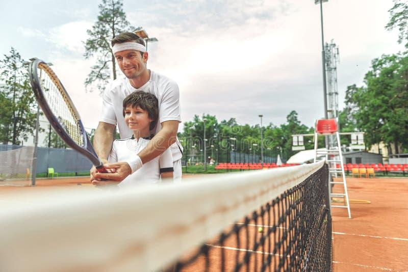 Filho de ensino do pai interessado para jogar o tênis imagens de stock