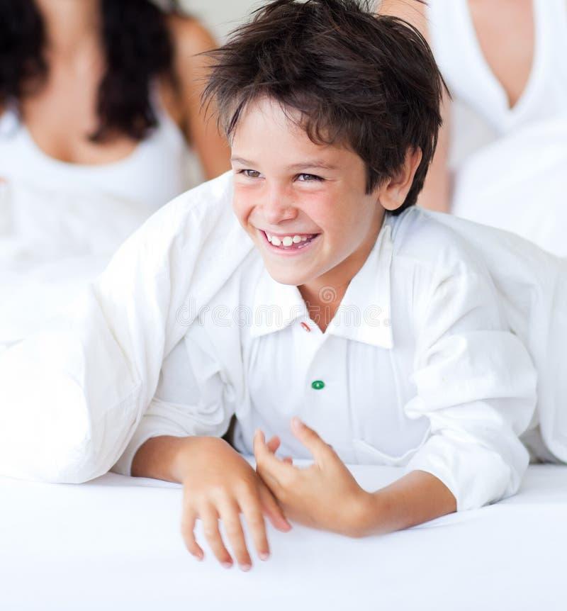 Filho de sorriso que tem o divertimento com seus pais na cama imagens de stock royalty free