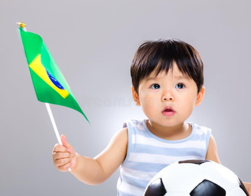 Filho do bebê que guarda a bola de futebol do amd da bandeira imagem de stock