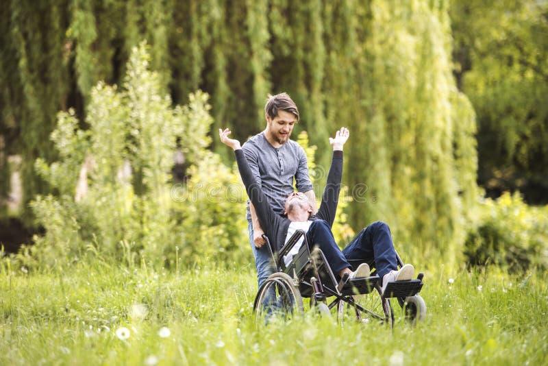 Filho do moderno que anda com o pai deficiente na cadeira de rodas no parque fotografia de stock