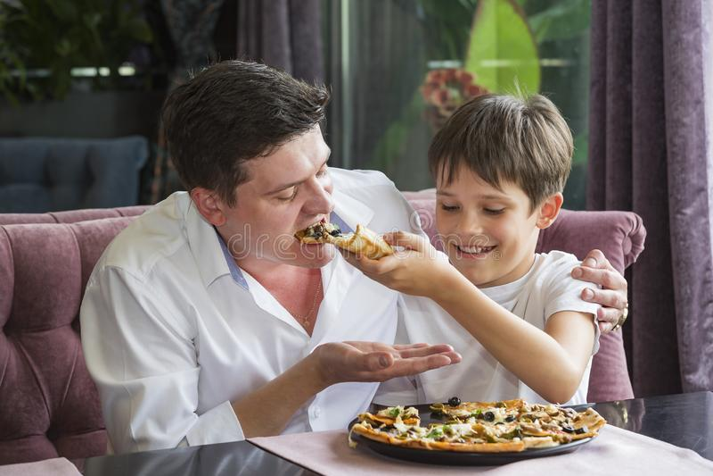 Filho do pai que come uma pizza italiana foto de stock royalty free