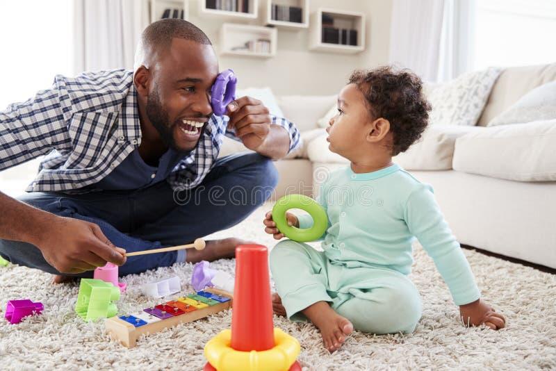 Filho do paizinho e da criança que tem o divertimento que joga em casa, perto acima imagens de stock