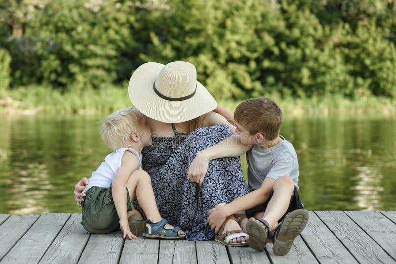 Filho dois pequeno que beija e que abraça sua mãe que senta-se em um cais no banco de rio imagem de stock