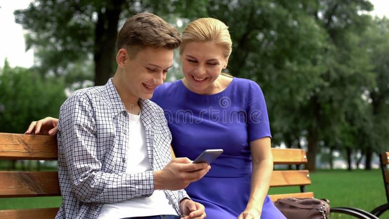 Filho e mãe que sentam-se nas fotos de observação do smartphone do banco tomadas durante a caminhada foto de stock royalty free
