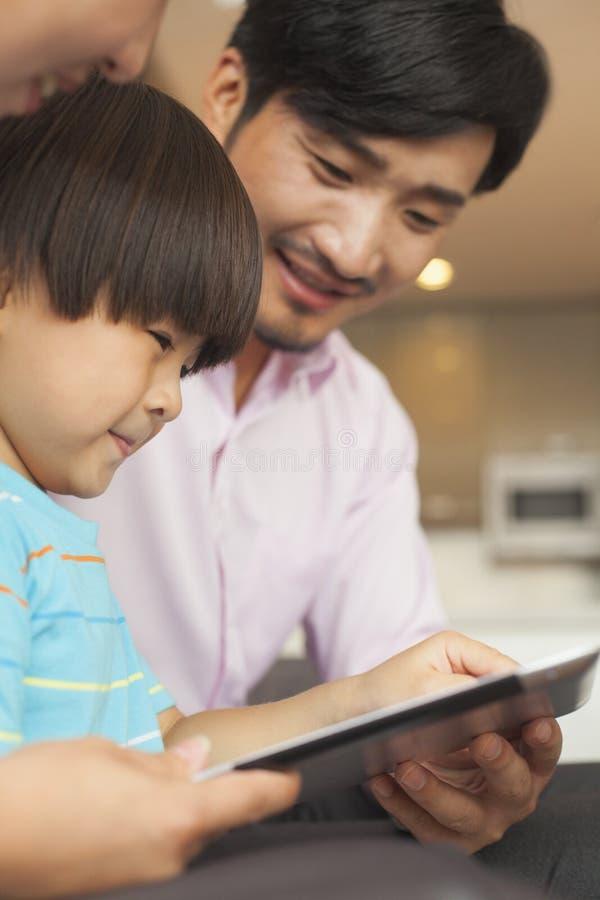 Filho e seus pais que usam a tabuleta digital foto de stock