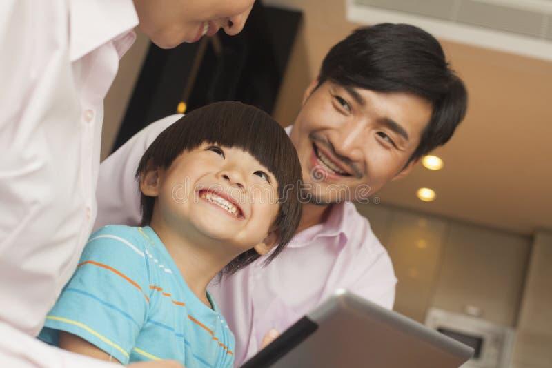 Filho e seus pais que usam a tabuleta digital imagens de stock