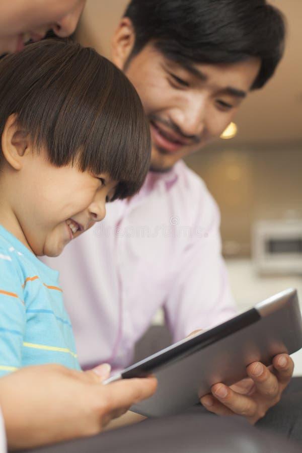 Filho e seus pais que usam a tabuleta digital fotos de stock royalty free