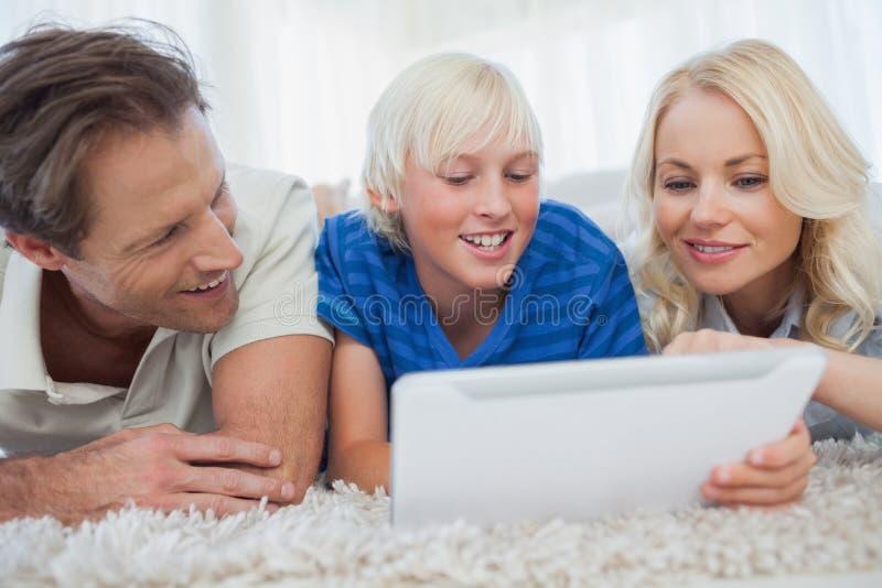 Filho e seus pais que usam uma tabuleta imagem de stock royalty free