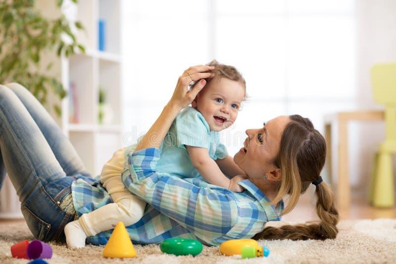 Filho feliz da mãe e da criança que encontra-se no assoalho e no jogo internos foto de stock
