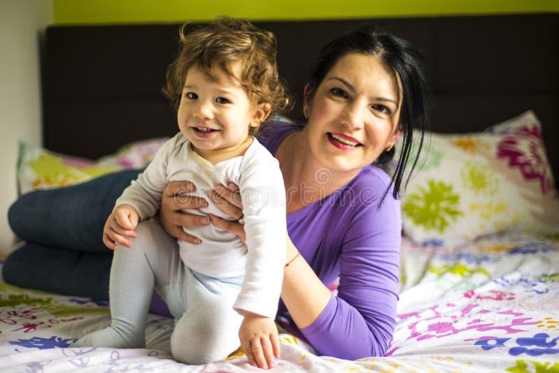 Filho feliz da mãe e da criança na cama imagens de stock