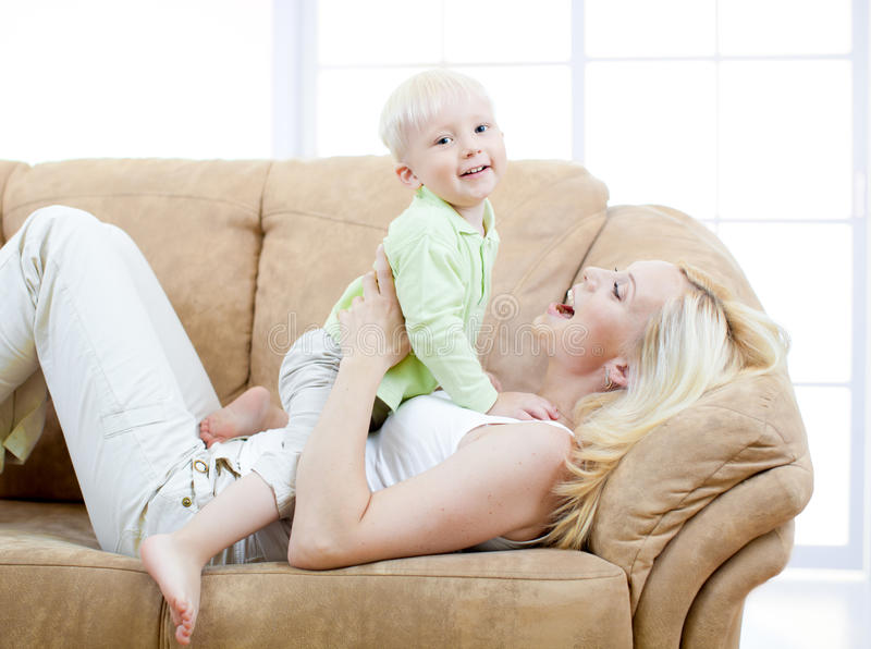 Filho feliz e matriz que jogam no sofá imagens de stock royalty free