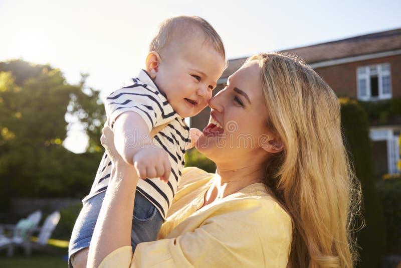 Filho levando do bebê da mãe nova fora no jardim do verão imagem de stock