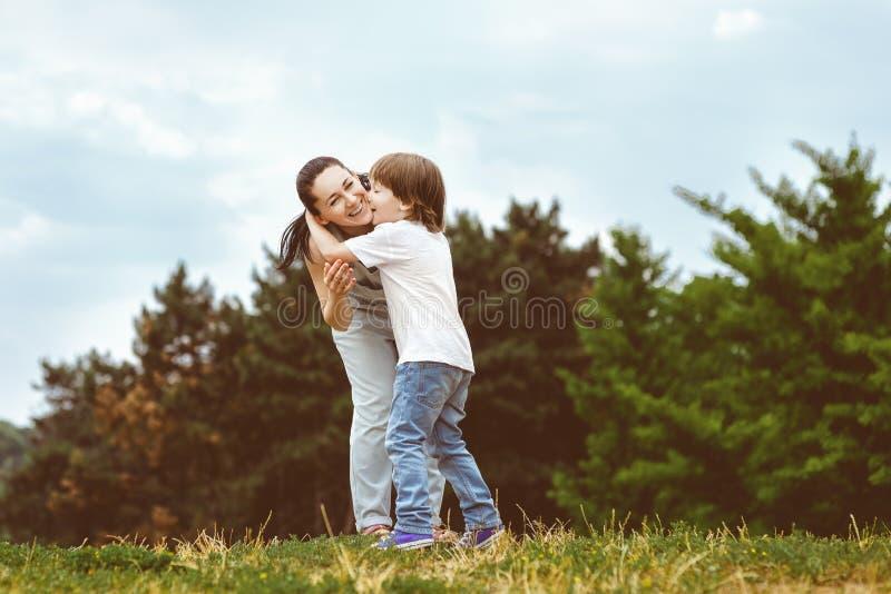 Filho loving que beija sua mãe feliz imagens de stock