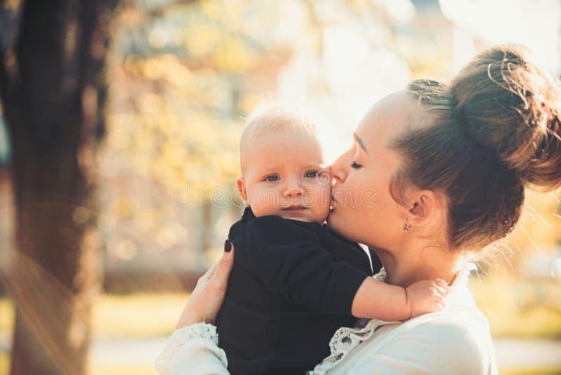Filho pequeno do beijo da mãe com amor Mulher com criança Mamã e bebê exteriores Conceito do dia de mães A família feliz aprecia fotografia de stock royalty free