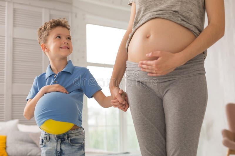 Filho pequeno feliz que olha sua mãe de antecipação foto de stock