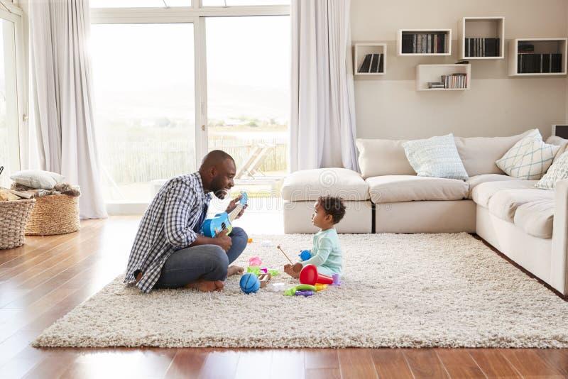 Filho preto do pai e da criança que joga na sala de estar imagens de stock royalty free