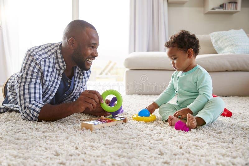 Filho preto do paizinho e da criança que joga no assoalho em casa, perto acima foto de stock