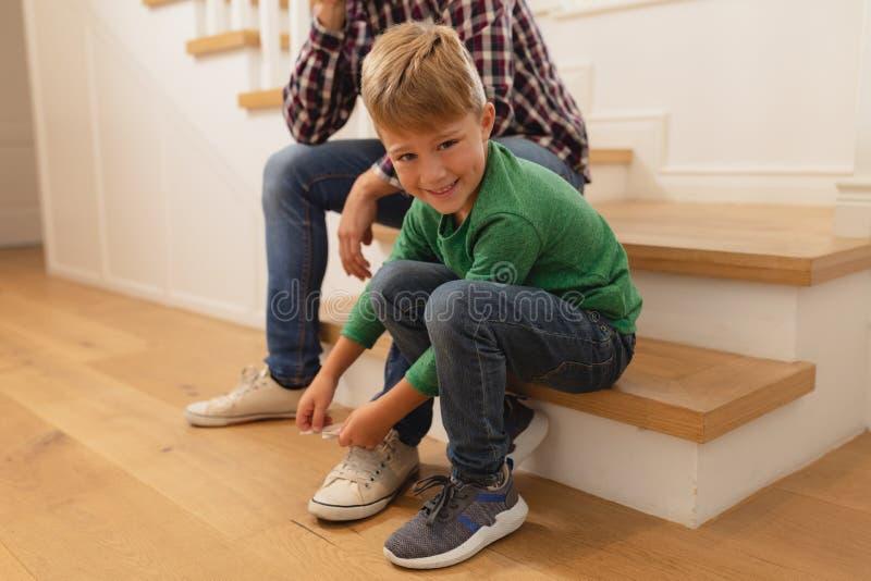 Filho que amarra seus laços do pai em uma casa confortável foto de stock