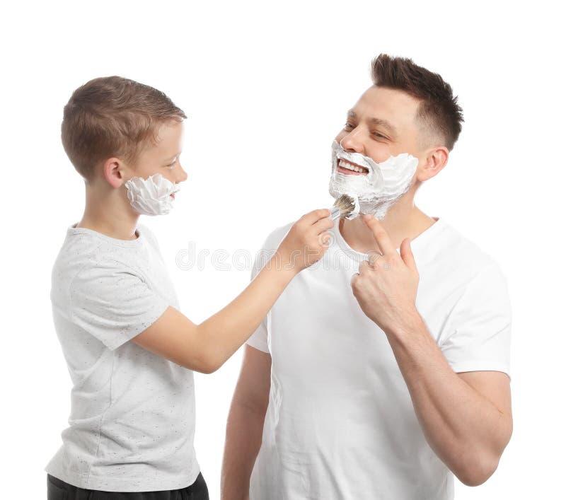 Filho que aplica-se barbeando a espuma na cara do paizinho, branca fotografia de stock