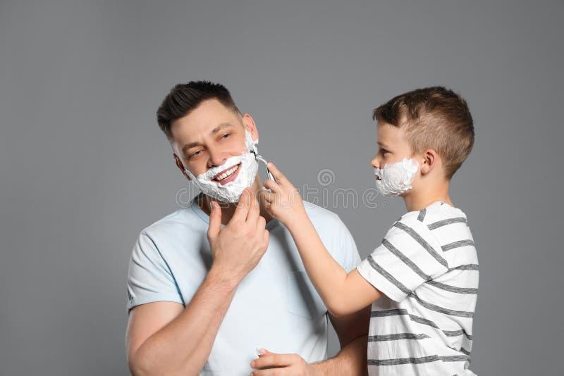 Filho que barbeia seu paizinho com a lâmina no cinza fotos de stock royalty free