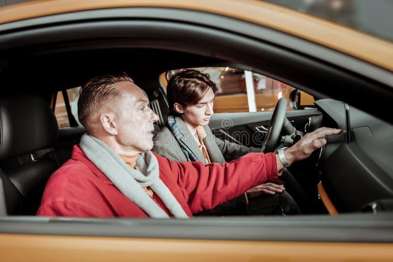 Filho que conduz quando seu pai considerável que senta-se perto dele fotos de stock