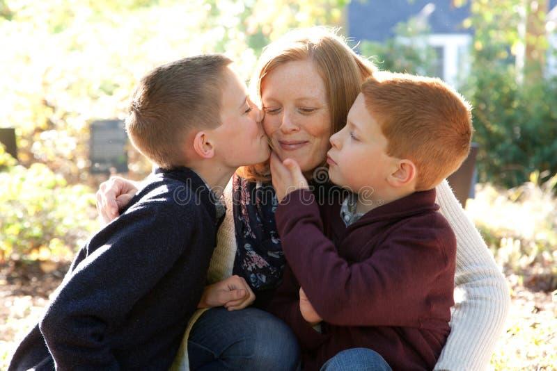Filhos que beijam a mãe feliz imagem de stock royalty free