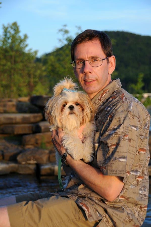 Filhote de cachorro de Shih Tzu e seu proprietário imagem de stock