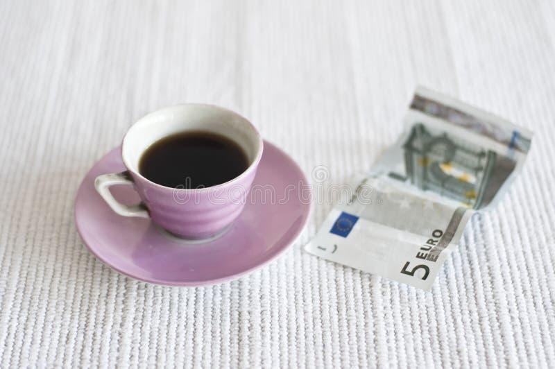 Filiżanka kawy i 5 euro notatka obrazy stock