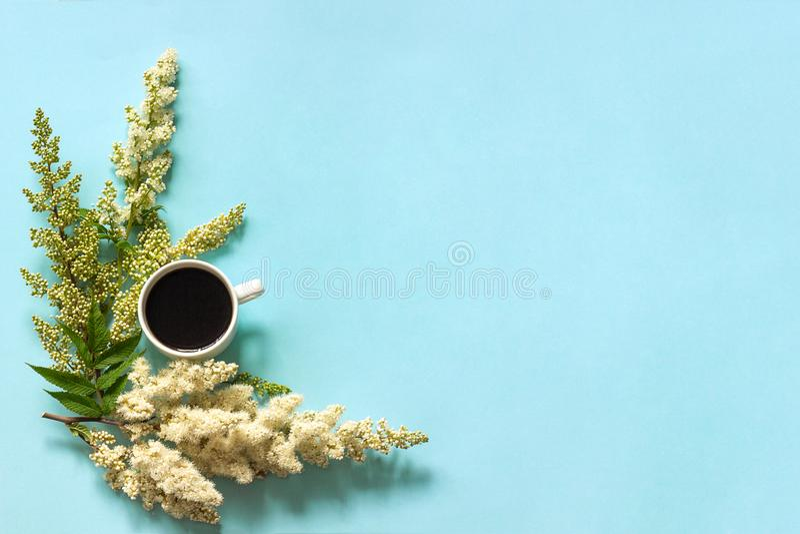 Filiżanka kawy i kwitnienie gałązki biali kwiaty na błękitnego papieru tła mieszkaniu kłaść Odgórnego widoku pojęcia dzień dobreg obrazy royalty free