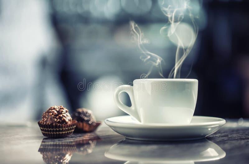 Filiżanka kawy z czekoladowymi tortami na prętowym biurku w noc klubie obrazy stock