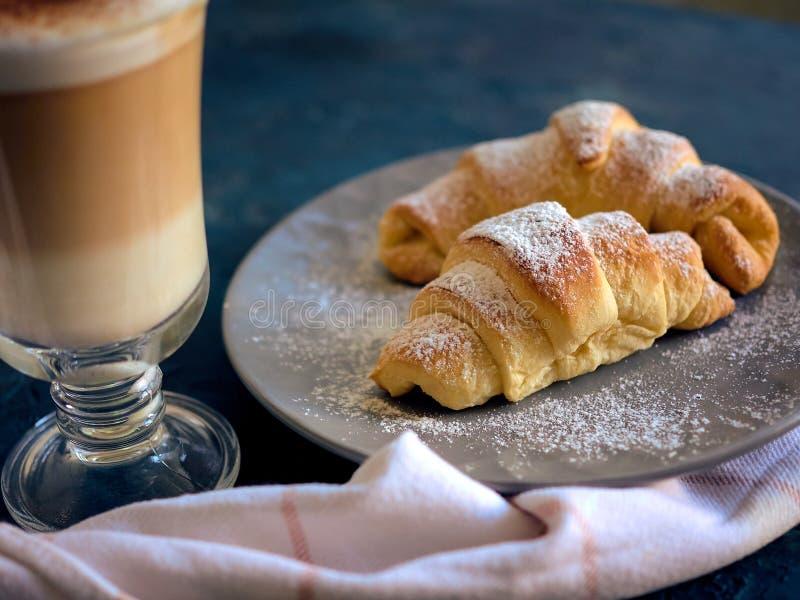 Filiżanka świeża kawa z croissants na zmroku - błękitny tło, selekcyjna ostrość zdjęcia stock