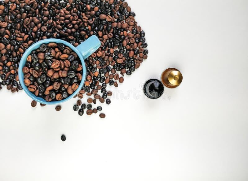 Filiżanka błękitna kawa z kawowymi fasolami otacza i dwa kawowej kapsuły z pustą przestrzenią, Odg?rny widok fotografia stock