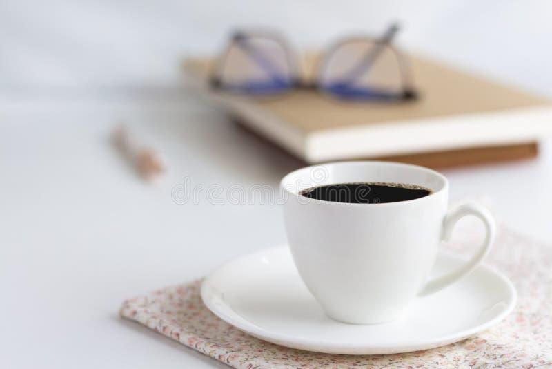 Filiżanka biała kawa, pióro i książki, umieszczamy na jaskrawych menchiach zdjęcia royalty free