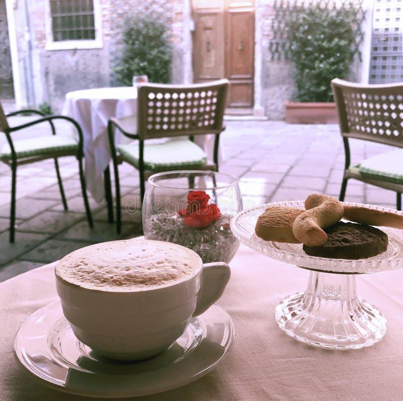 Filiżanka capuccino kawa na outside kawiarnia stole z widokiem spokojnej Wenecja ulicy obraz stock