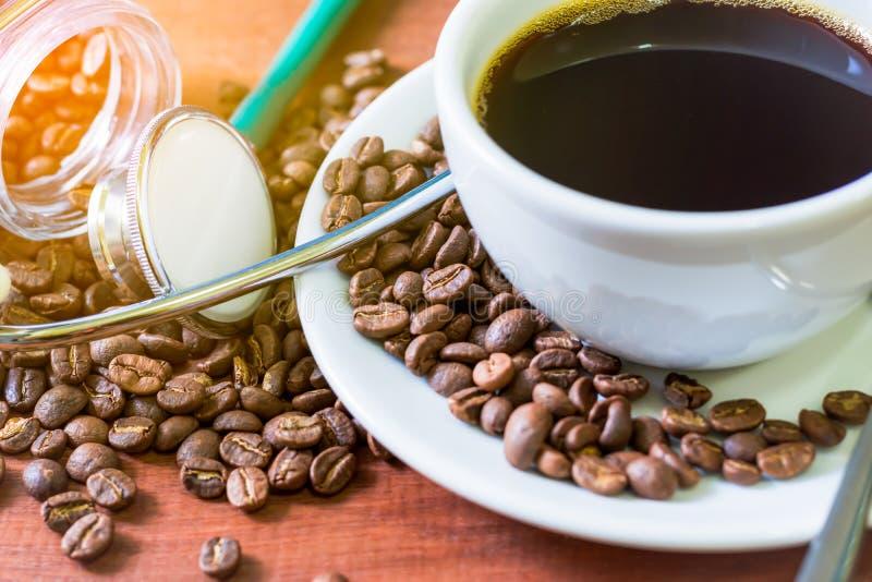 Filiżanka ciemna kawa z kawowymi fasolami i stetoskopem na drewnianym tle Zdrowia pojęcie co jak napój kawa obraz royalty free