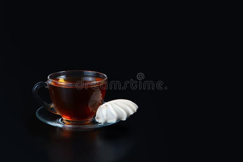 Filiżanka czarna herbata na czarnym odosobnionym tle Beza obok filiżanki Zaperzony deser fotografia stock