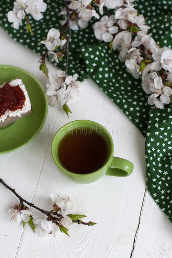 Filiżanka czarna herbata na zielonej pielusze, domowej roboty żyto chleb z miękkim kremowym serem i dymiący wysuszeni pomidory, g zdjęcie royalty free