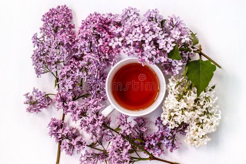 Filiżanka czarna herbata z bukietem bez na białym stole fotografia stock