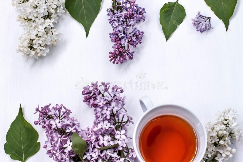 Filiżanka czarna herbata z bukietem bez na białym stole zdjęcie royalty free
