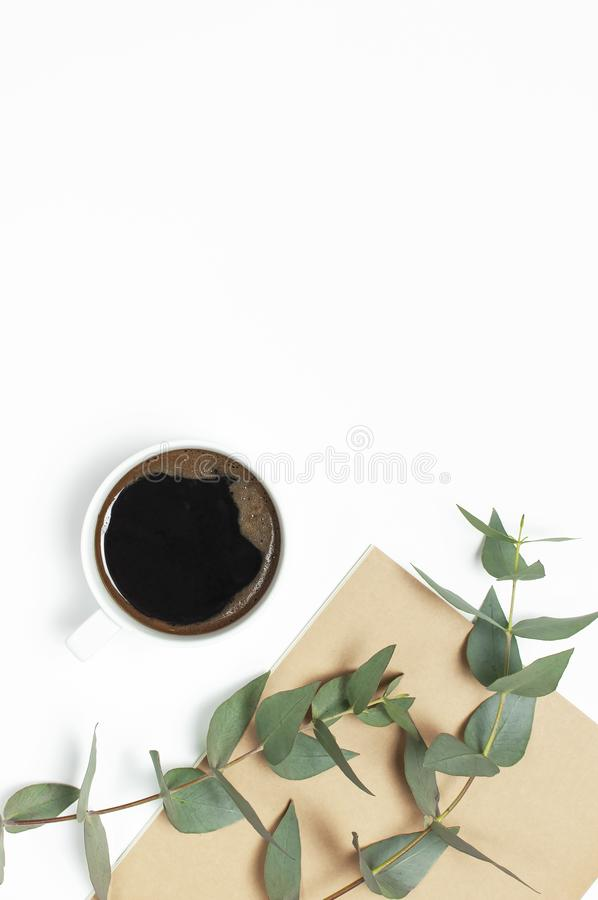 Filiżanka czarna kawa, notatnik, dzienniczek, pióra, zielony sprig eukaliptus na białym tle Mieszkanie nieatutowy, odg?rny widok, zdjęcia stock