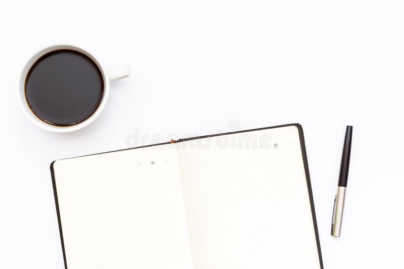 Filiżanka czarna kawa, otwiera dzienniczek i pisze na białym tle minimalny biznesowy pojęcie fotografia royalty free