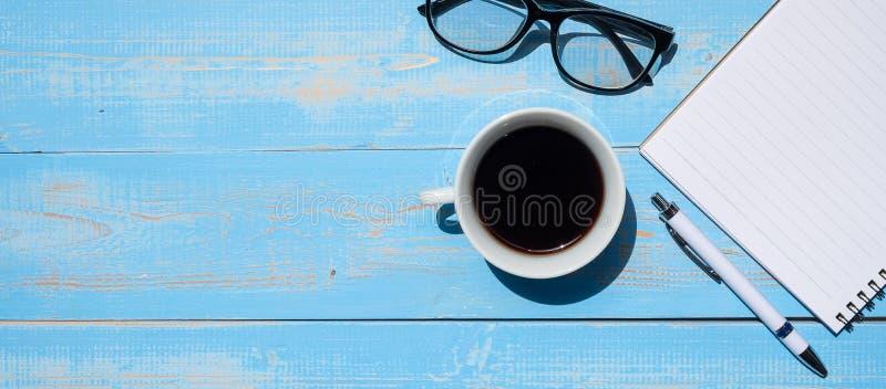 Filiżanka czarna kawa z biurowymi dostawami; pióra, notatnika i oczu szkła na błękitnym drewnianym stołowym tle, zdjęcia royalty free