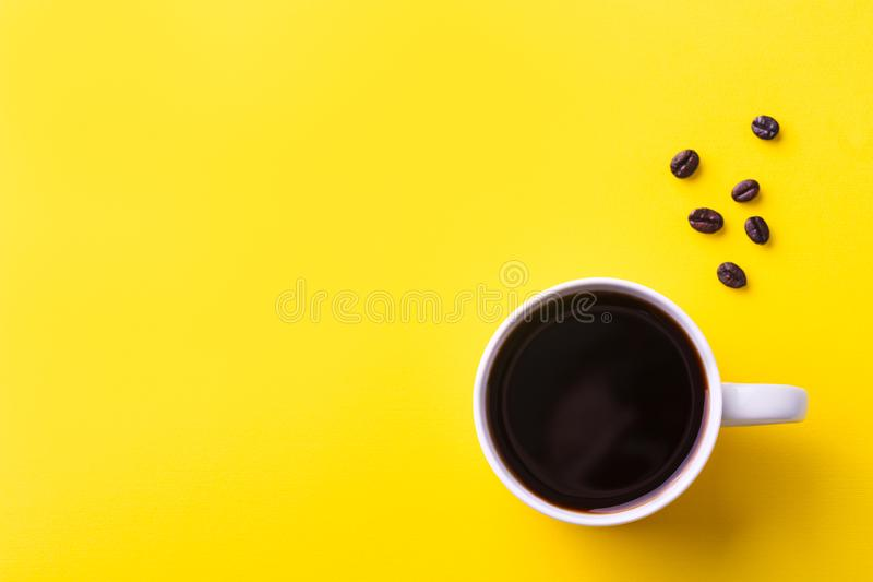 Filiżanka czarna kawa z kawowymi fasolami na żółtym tle Odg?rny widok kosmos kopii fotografia royalty free