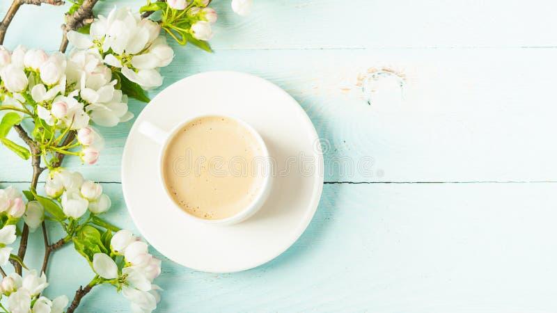 Filiżanka gorąca aromatyczna kawa i kwitnie gałąź jabłoń na drewnianym błękitnym tle P?aski uk?ad fotografia royalty free