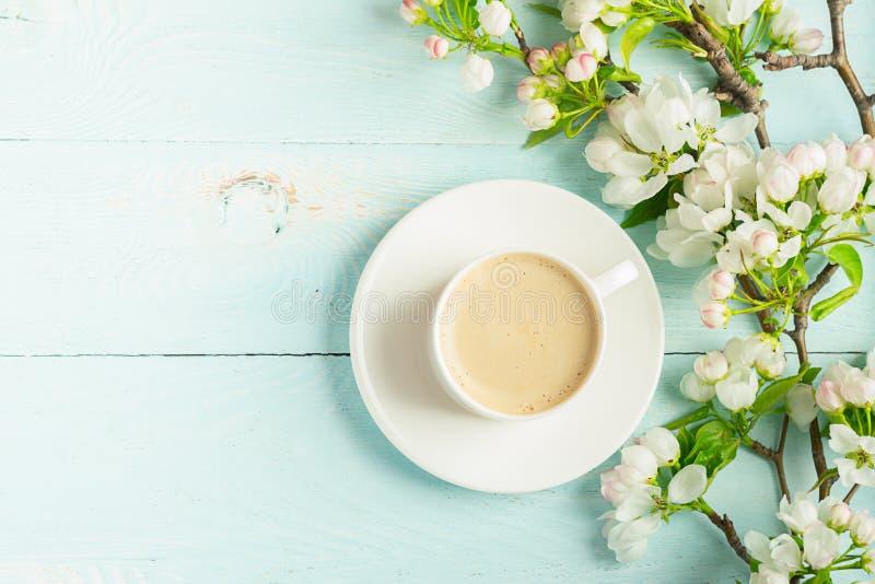 Filiżanka gorąca aromatyczna kawa i kwitnie gałąź jabłoń na drewnianym błękitnym tle P?aski uk?ad obrazy royalty free