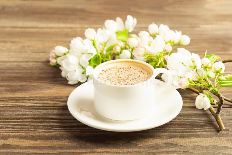 Filiżanka gorąca aromatyczna kawa i kwitnie gałąź jabłoń na drewnianym tle P?aski uk?ad kosmos kopii zdjęcie royalty free