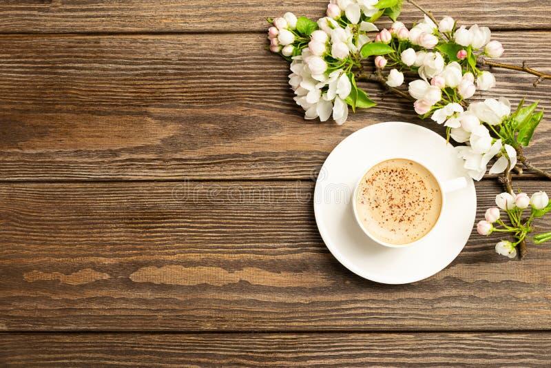 Filiżanka gorąca aromatyczna kawa i kwitnie gałąź jabłoń na drewnianym tle P?aski uk?ad zdjęcie stock