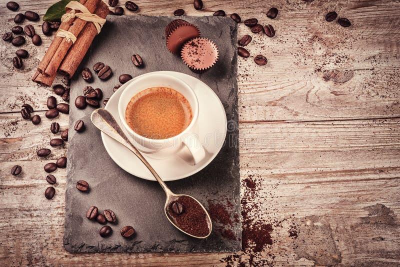 Filiżanka gorąca czarna kawa w położeniu z piec kawowymi fasolami fotografia royalty free