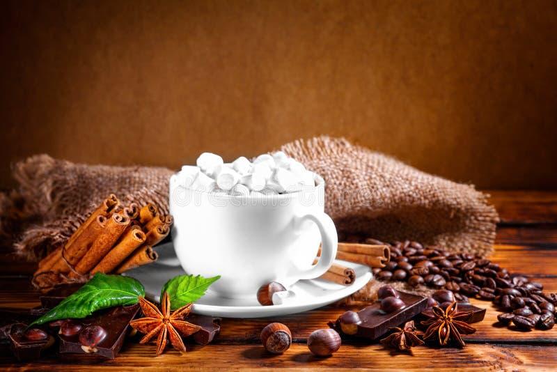 Filiżanka gorąca czekolada, cynamonowi kije, dokrętki i czekolada, dalej zalecamy się obrazy royalty free