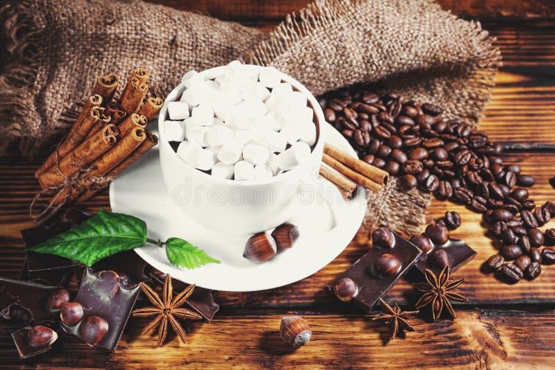 Filiżanka gorąca czekolada, cynamonowi kije, dokrętki i czekolada, dalej zalecamy się fotografia royalty free